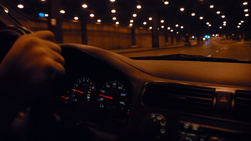 Hands on steering wheel driving through city tunnel at night time lapse