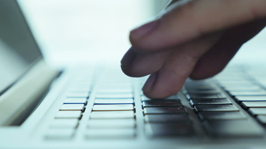 Hands touch typing on a laptop keyboard