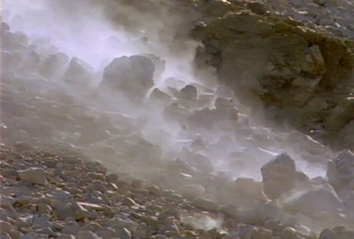 Boulders and smaller rocks roll and slide down a hill during a landslide.