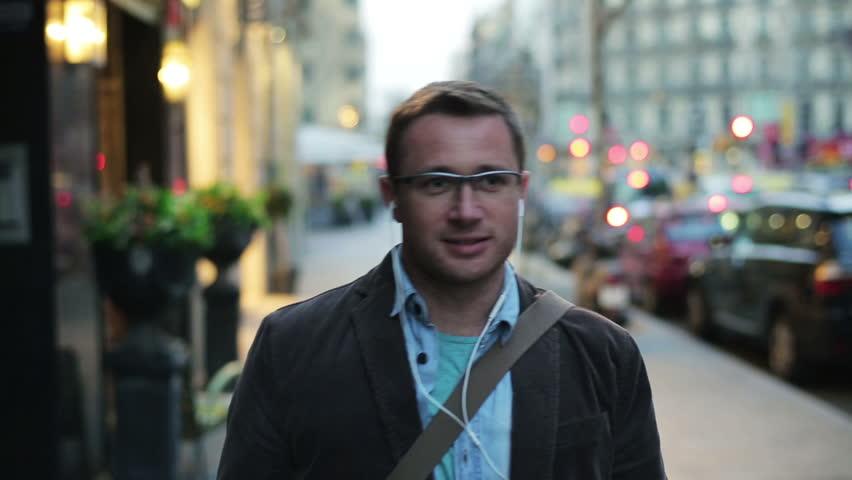 Man walking along the street and listening an mp3 player    Shutterstock HD Video #6192914