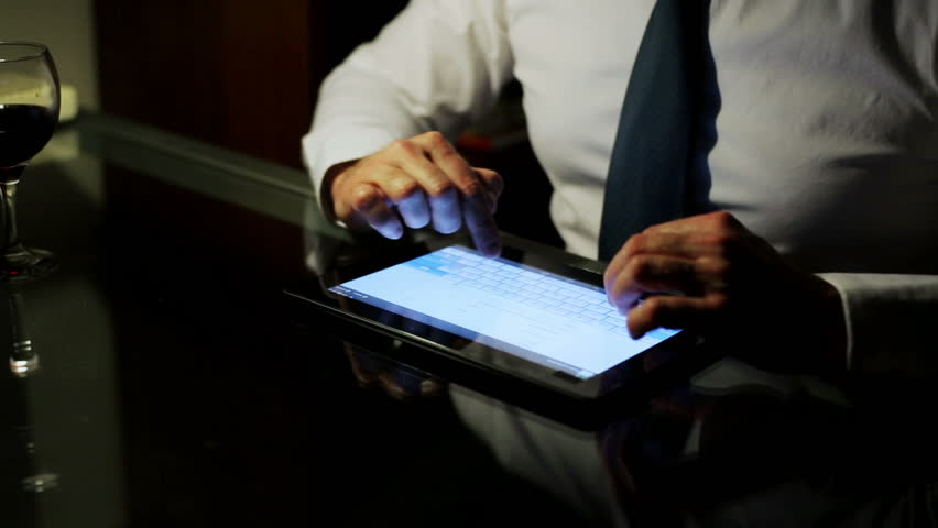 Businessman writing an e-mail on tablet at night, closeup.
