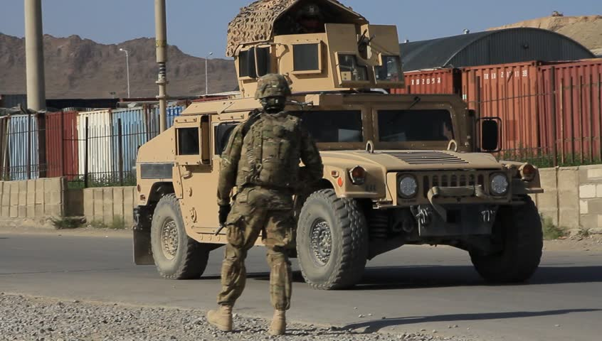 Humvee stops to talk with soldier before leading convoy out from base in afghanistan
