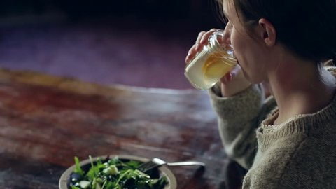 Woman at the table drinking lemonade with salad on table