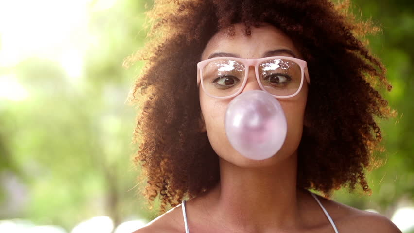 Happy African American Girl having fun blowing bubble gum in slow motion