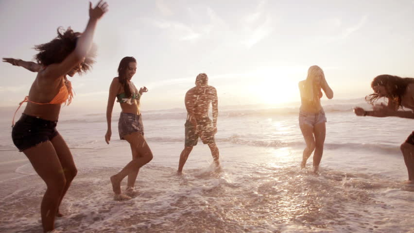 Friends splashing water at the beach in slow motion #6259328