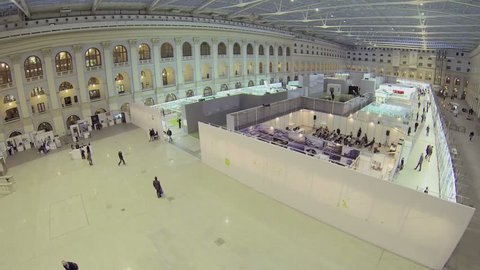 MOSCOW - DEC 24, 2013: People sit in conference hall and walk by pavilions during Festival of Architecture at exhibition center Gostiny Dvor. Aerial view