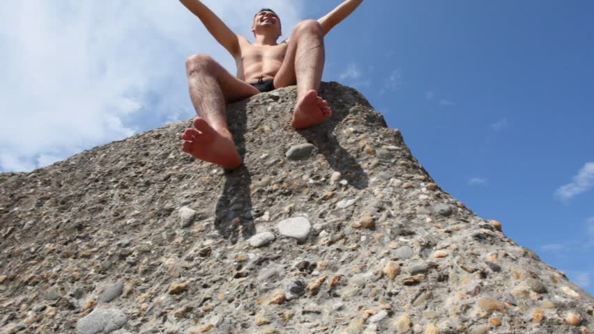 man sitting on boulder in beach, sky with clouds in background