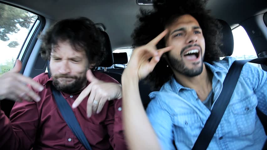 Two drunk friends in car celebrating after party singing and dancing driving car