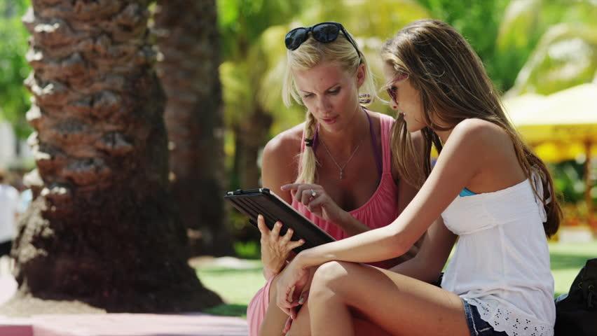 Medium Shot Young women using digital tablet outdoors / South Beach, Miami, Florida, USA   Shutterstock HD Video #6319571