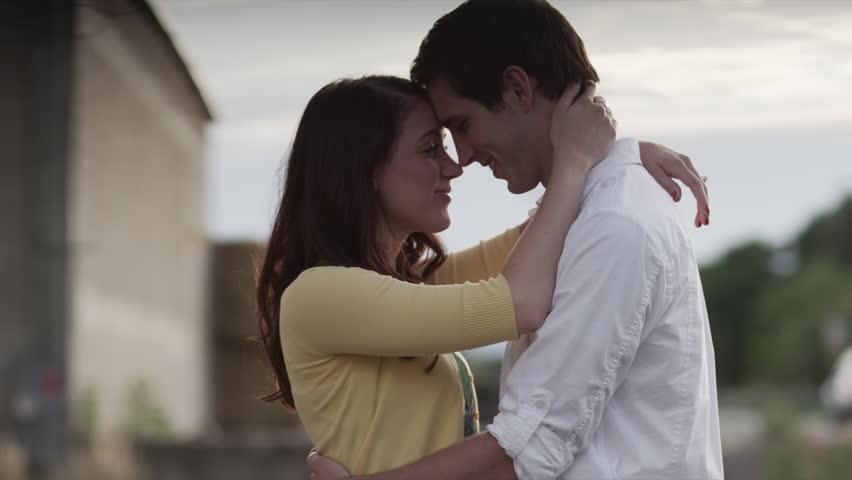 SLO MO Medium Shot Young couple kissing outdoors