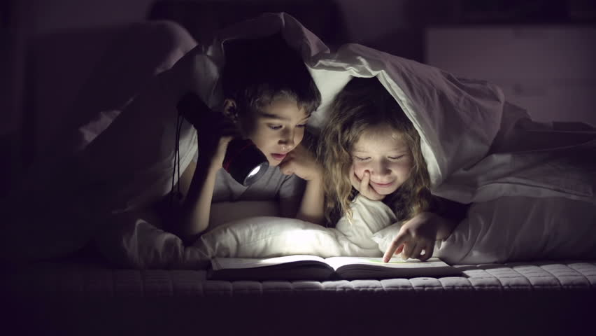 Children with flashlight reading