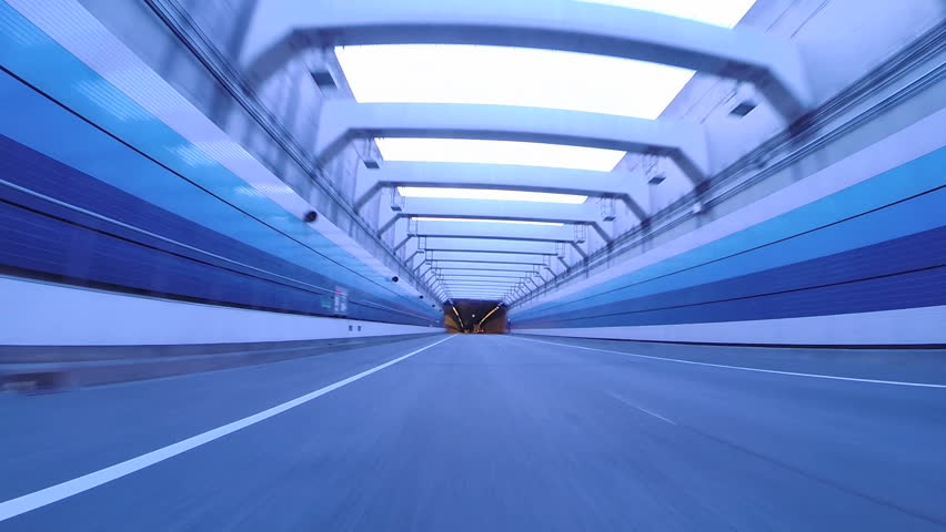 (Driver POV) Twilight drive through Tokyo Bay Area's futuristic architecture through tunnels and highways. Symmetrical arches over the tunnel on the Bayshore Highway.