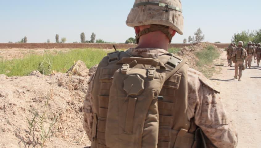 Closeup of back of US Marine as he walks on patrol down dusty dirt road in