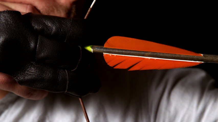 Man shooting an arrow on black background in slow motion