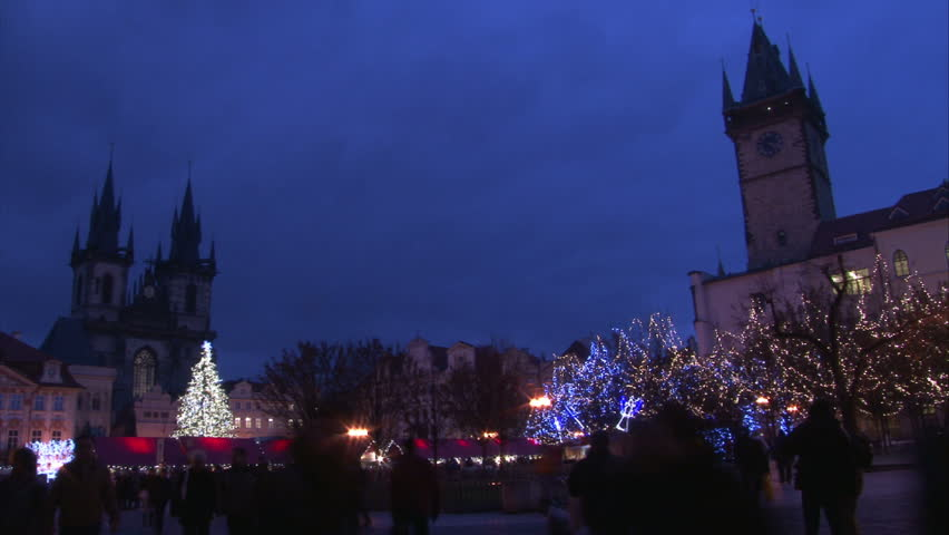 Sunset with walking people on Old Town Square with St. Teyn gothic cathedral in Prague during Christmas market. Time lapse