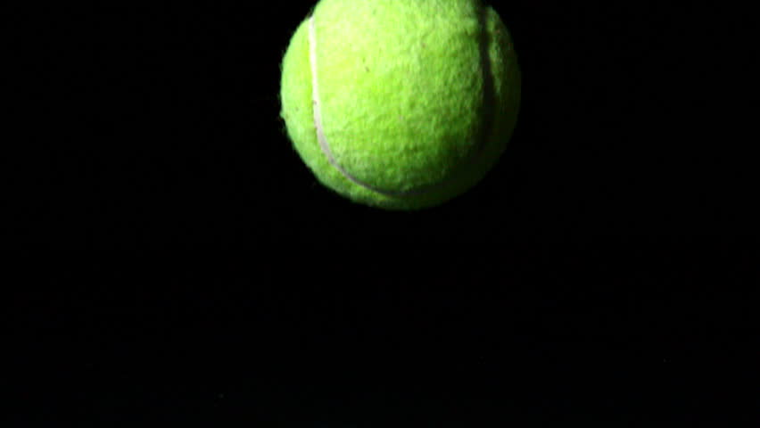 Tennis ball falling on black background in slow motion