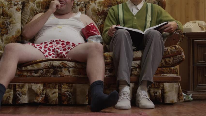 Medium Shot Obese man wearing underwear sitting on sofa next to geek reading book Orem