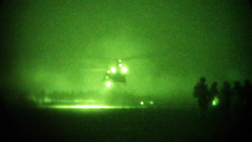 Night Vision: Chinook helicopter lands in desert at night and camera pans to waiting soldiers