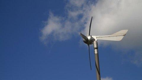 Wind turbine against a blue cloudy sky