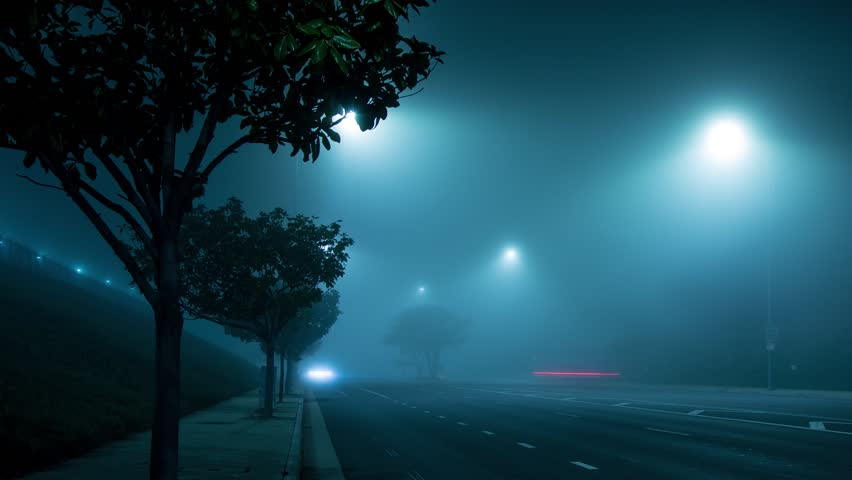 4K. Street intersection traffic at foggy night in Los Angeles, California. Zoom out. Timelapse.
