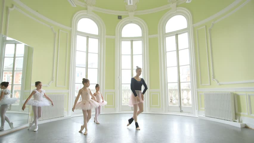 Female Ballet Dancer leads three young Ballerinas, sweeping across the Studio floor
