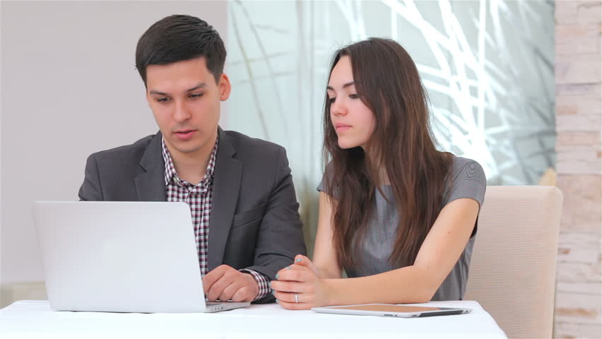 Young attractive business man and woman discussing comparing the data on the laptop | Shutterstock HD Video #6448583