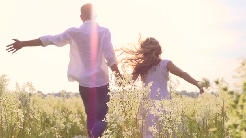 Happy couple having fun outdoors. Couple running away being excited with the freedom of the countryside. Young Man and woman holding hands and running through a field with wild flowers. Slow motion #6462638