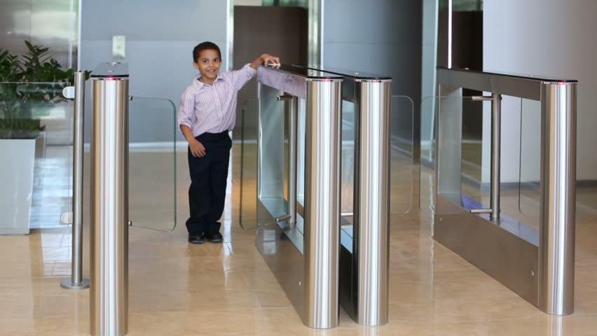 Cute mulatto boy passes through glass turnstile in business center | Shutterstock HD Video #6485963