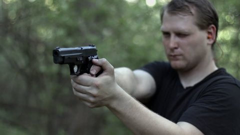 Close, frontal view of man firing a .44 caliber pistol in woodland.  Muzzle flashes visible.  Recorded in 4K, Ultra High Definition.