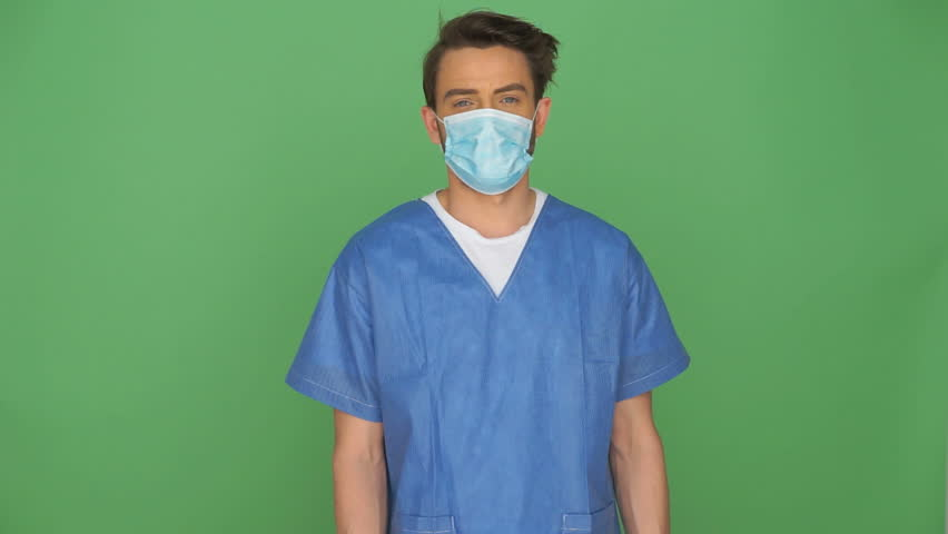 Doctor or male nurse in scrubs and a mask wearing gloves standing against a green background about to remove his mask with his hand, with copyspace | Shutterstock HD Video #6487151