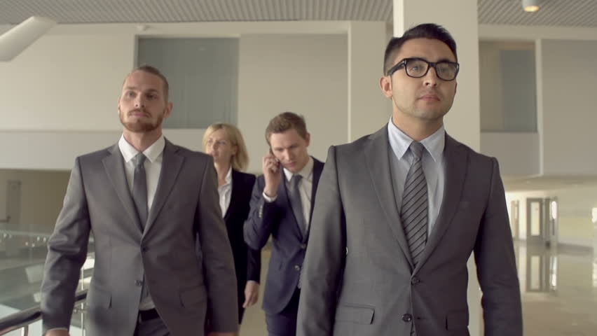 Two guys passing by camera, focus shifting to woman and man walking towards camera in slow motion #6493550