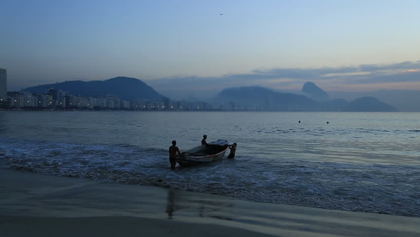 Fishermen push their boat out to sea in Brazil at sunset #6514307