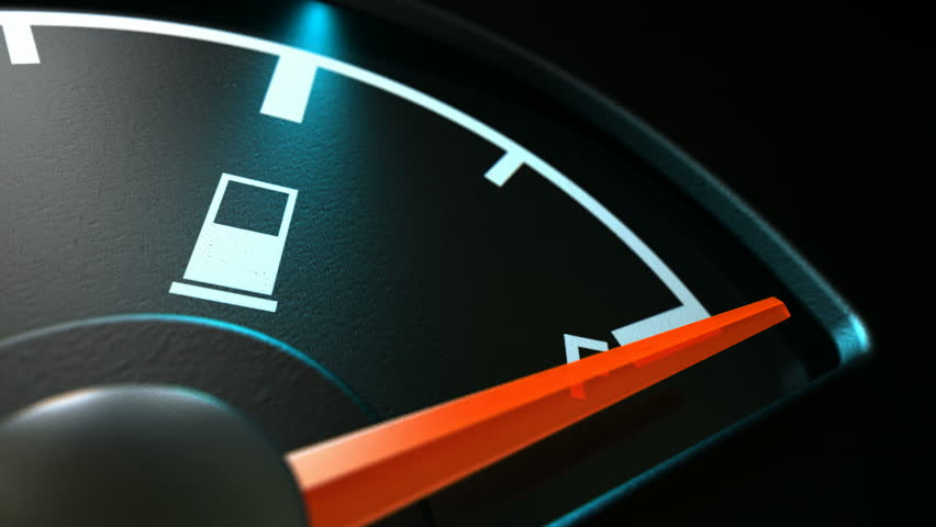 An extreme closeup time-lapse of a backlit illuminated gas gage showing the needle decreasing dramatically from full to empty