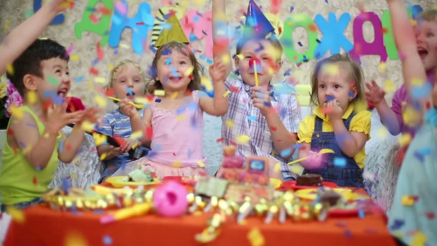 Seven little kids sit at red table with cake and throw confetti at birthday party. Inscription Happy Birthday on wall | Shutterstock HD Video #6530561