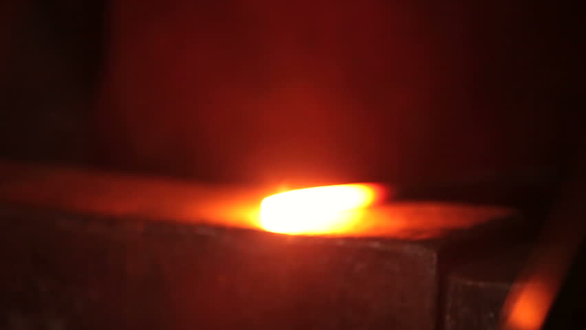 Blacksmith strikes red hot iron, sparks fly, closeup