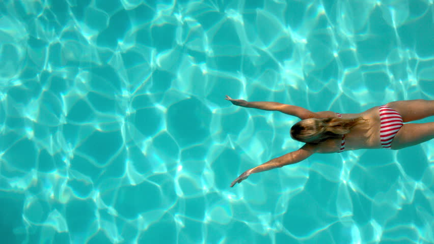 Caucasian woman swimming in the pool underwater overhead in slow motion