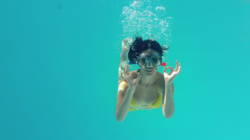 Gorgeous brunette in yellow bikini swimming underwater wearing snorkel in slow motion