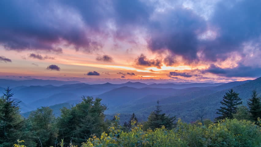 Vibrant Blue Ridge Mountain Sunset seen from Caney Fork Overlook on the Blue Ridge Parkway Featuring Green Forestry, Blue Layers of Mountains and Glowing Orange and Pink Sky near Asheville, NC.