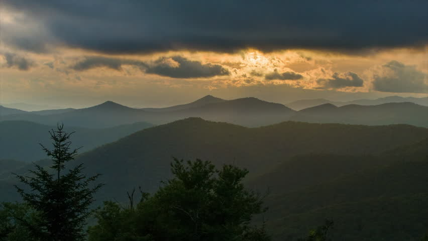 Moody Scene at Dusk Over the Dark Layers of the Appalachian Mountains near Asheville in Western North Carolina Featuring Golden Sun Rays Illuminating the Clouds over the Forest.
