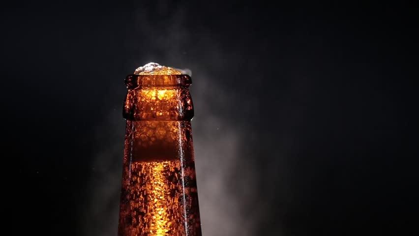 open wet beer bottle isolated on black
