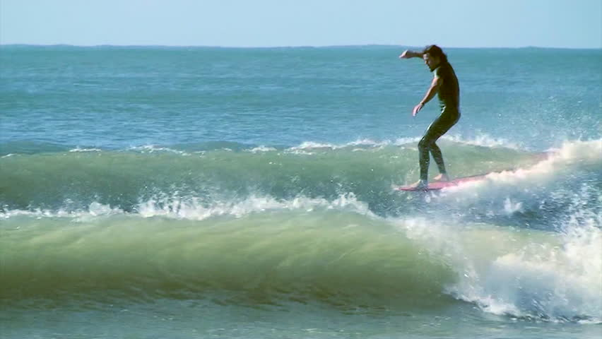 Australia, California,Hawaii, Mexico and Micronesia, 2011. A surfer riding a wave standing up on the tip of a surfboard, long shot   Shutterstock HD Video #6595268