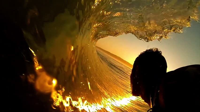 High contrast POV shot of silhouetted surfer as he rides through the barrel of a dark orange wave, with the sun setting ahead of him #6596987