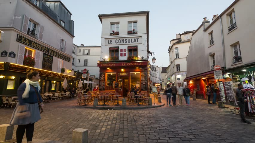 PARIS, FRANCE - MAY 15, 2014: Tourists walking in front of Le Consulat, a typical cafe in Montmartre area. Time lapse movie, transition day to night.