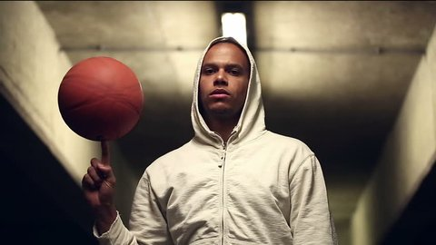 Portrait of a serious looking hooded basketball player spinning a basketball at night