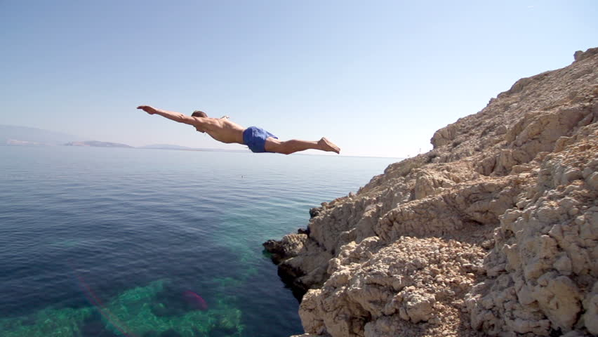 Slow Motion Of A Very Fit Man Jumping Of The Cliff Head First Into Clear Blue Water And Making A Splash. Sun Flares. #6605894