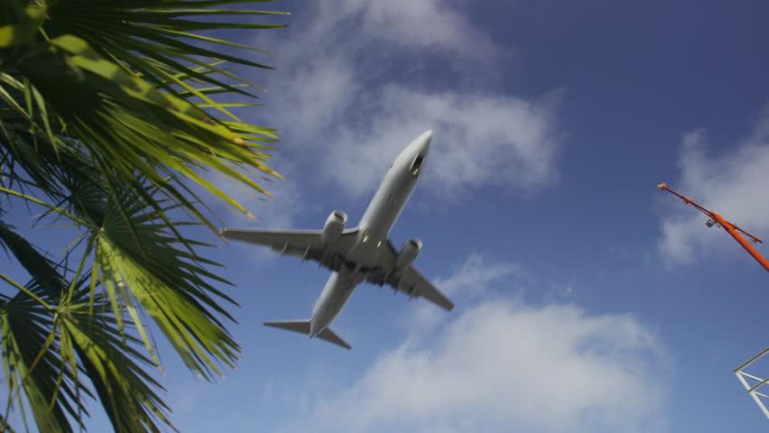 Passenger plane lands overhead through blue sky