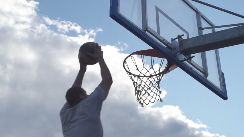Spectacular Low Angle Rearview Shot Of Professional Basketball Player Scoring A Basket By Alley-Oop And Hanging On The Hoop #6640535