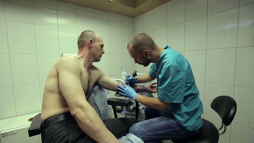 Tattoo artist working. Man draws on his arm woman's face. Long to medium shot. Tattoo salon. HD shot with slider. SESSION KEYWORD: uzhursky001 | Shutterstock HD Video #6642050