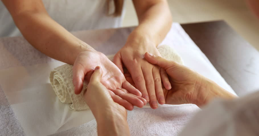 Beauty therapist massaging customers hands at the nail salon #6642527
