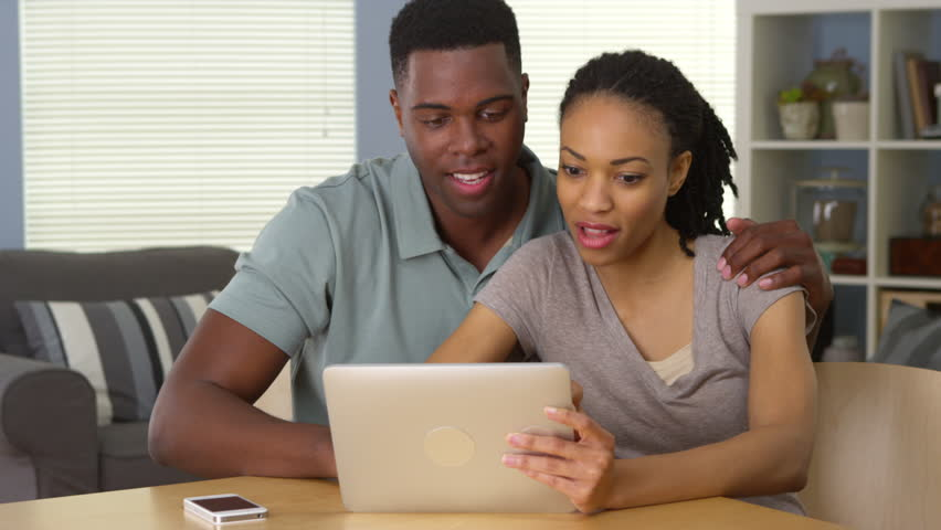 Happy young black couple using tablet computer together laughing | Shutterstock HD Video #6645683